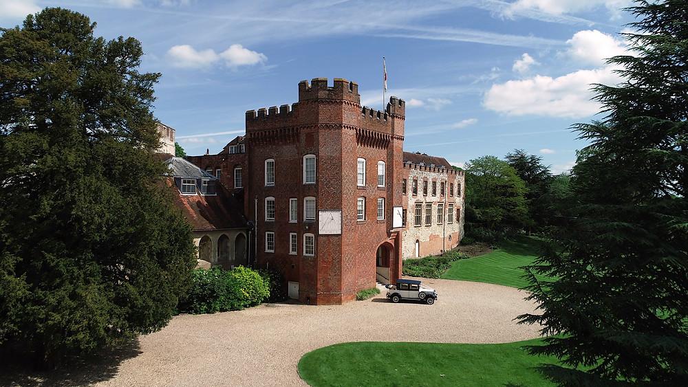 a videographers drone shot of farnham castle which is a wedding venue in surrey