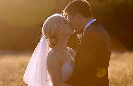 bride and groom kissing in a sunset during their wedding in Surrey taken by a videographer