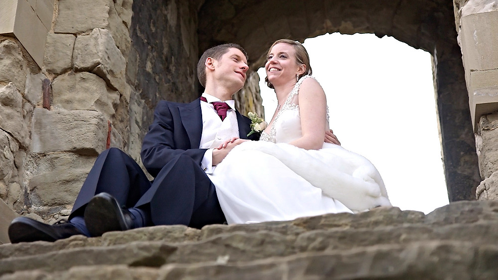 bride and groom sitting at farnham castle