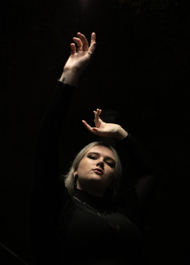 darkly lit headshot of young woman with hands and face lit