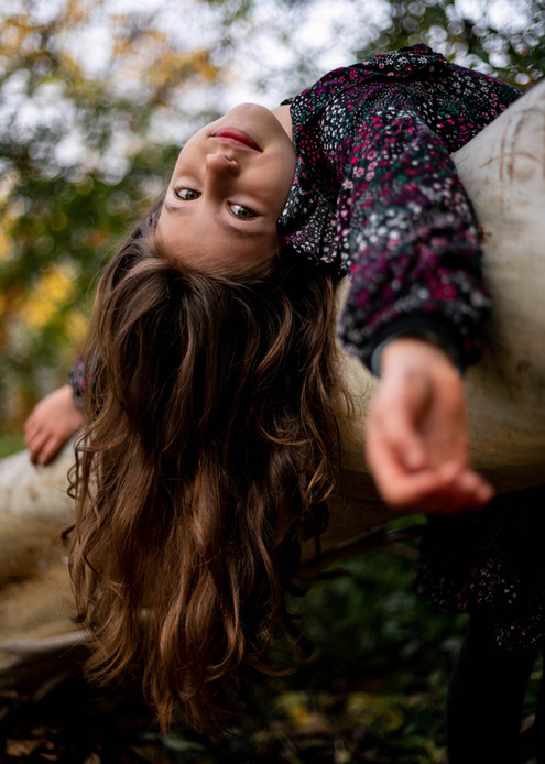portrait of girl hanging upside down on tree trunk