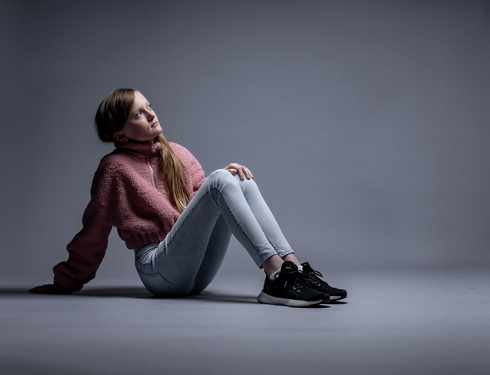 Girl in pink jumper and jeans, lit from above. Looking thoughtful. K...phy. Kent studio photographer