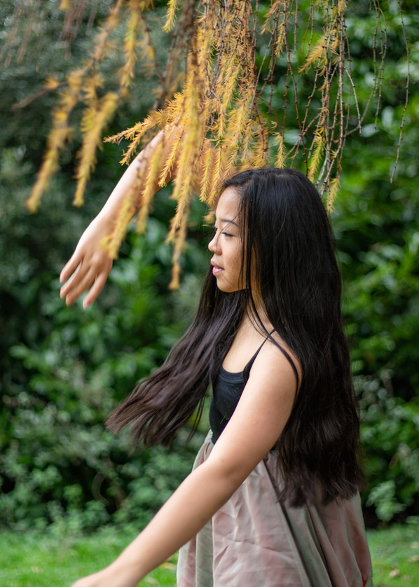 teenage girl dancing under a tree