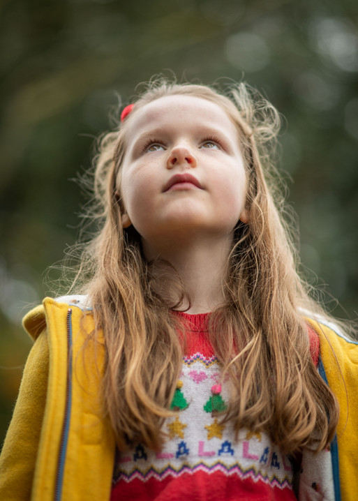 young girl looking up yellow coat