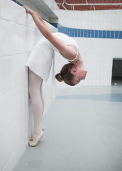 dancer in white leotard in backbend