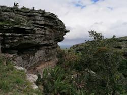 Landscape of layered rocky cliffs on 2 sides of gorge