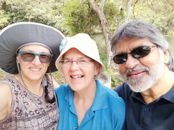 Three adults smiling, looking into camera