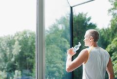 Homem bebendo água e olhando para horizonte