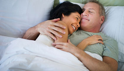 1140-happy-mature-couple-laying-in-bed.i