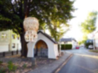 Dorfplatz mit Heiligenhaus und Eierkrone 2018 An de Löng