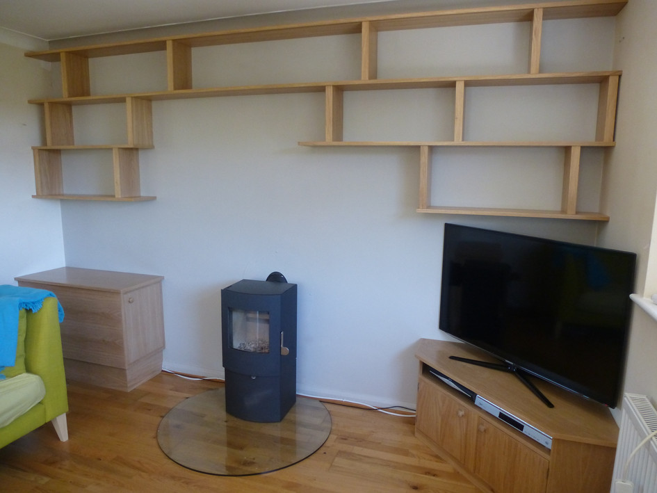 Asymmetrical shelving with TV unit and log store