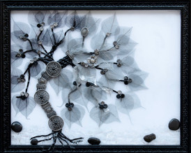 """Funky metal belt as tree trunk with leather strips for branches. Skeleton leaves and decorative little discs comprise the canopy and the ground is textured clear glass with black pebbles.  18"""" x 22""""  $335 FREE Shipping in US"""