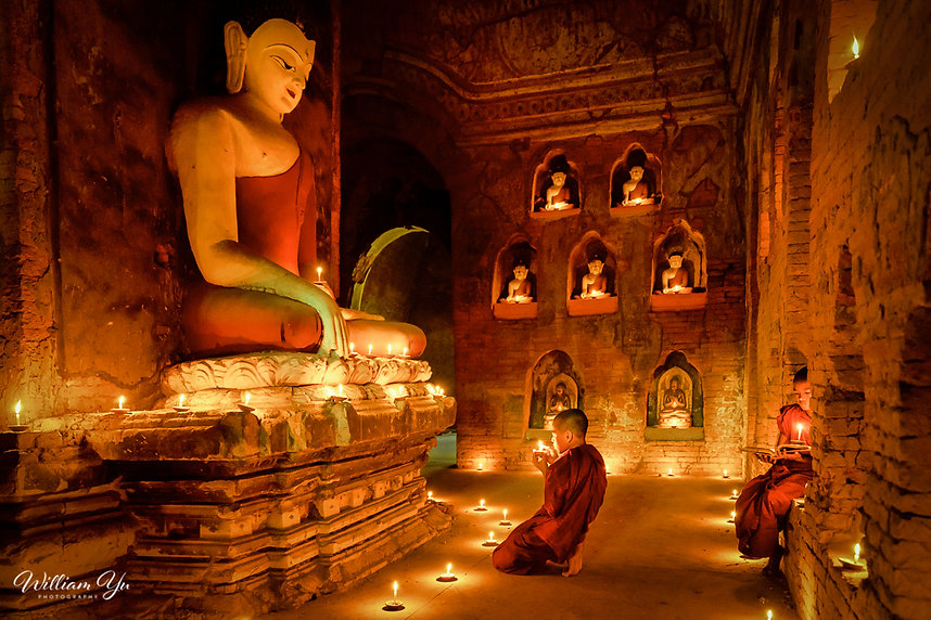 Young monk praying inside pagoda