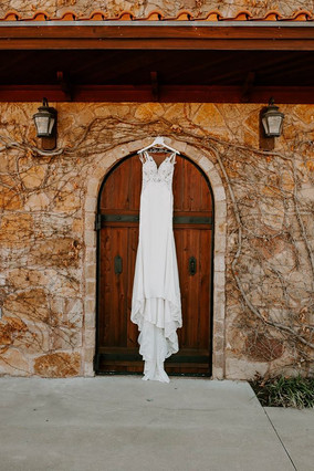 An absolutely STUNNNING photo of a brides dress in our vines in front of one of our wooden doors!