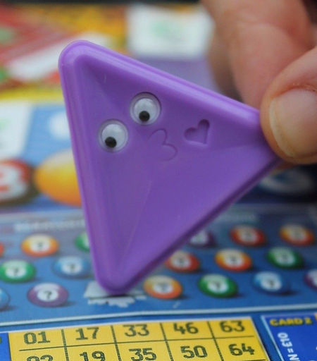 Picture of a purple scrapemate lucky scratchcard scraper called kissy scratching off a lottery scratchard