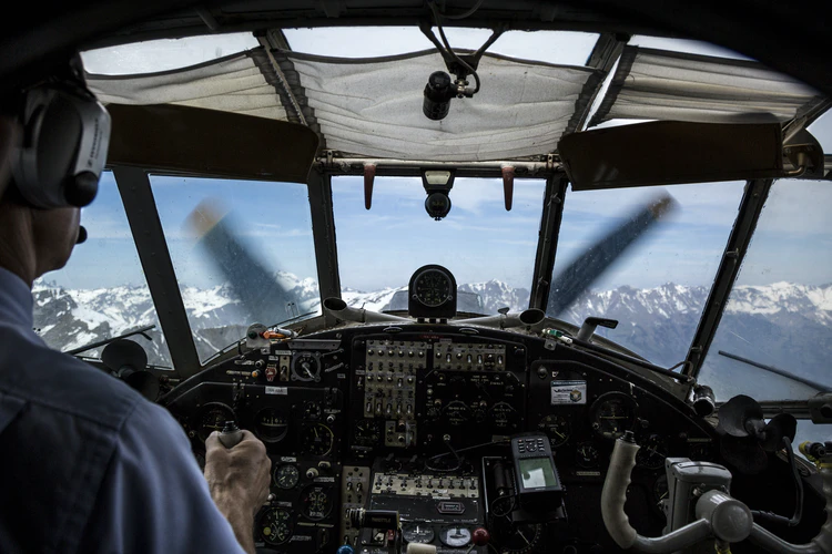 A pilot in the cockpit of a plane near the Swiss Alps