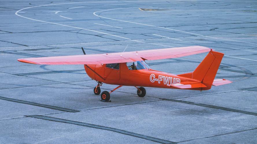 A small orange airplane waits on the tarmac