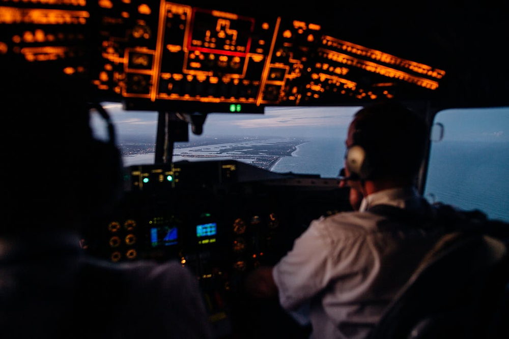 pilots in aircraft cockpit flying over sea