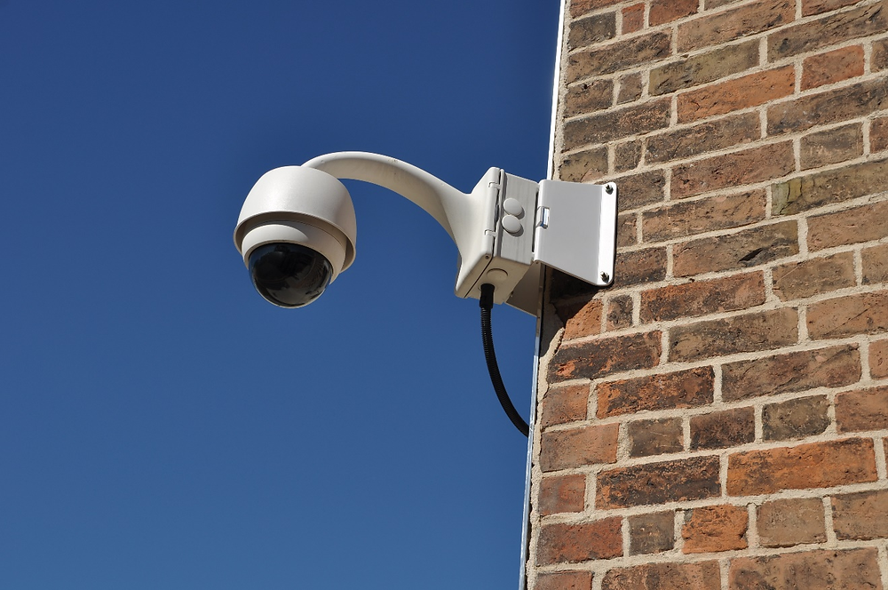 A surveillance analog camera attached to a brick wall building.