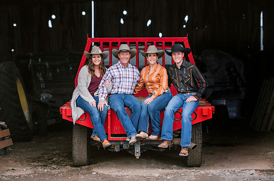 Family sitting on red dodge flabed, Family Ranch, Family Farm, Everyone wearing cowboy hats, Hay and Cattle For Sale, Mother and Father and their son and daughter