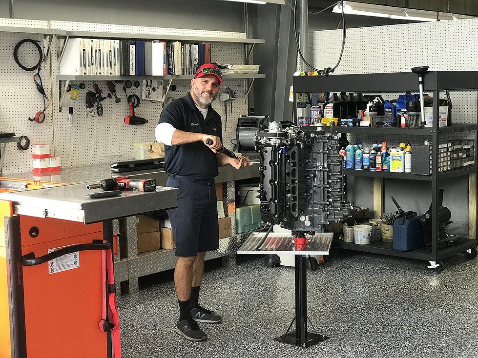 Service Department Technician works on a Mercury Engine