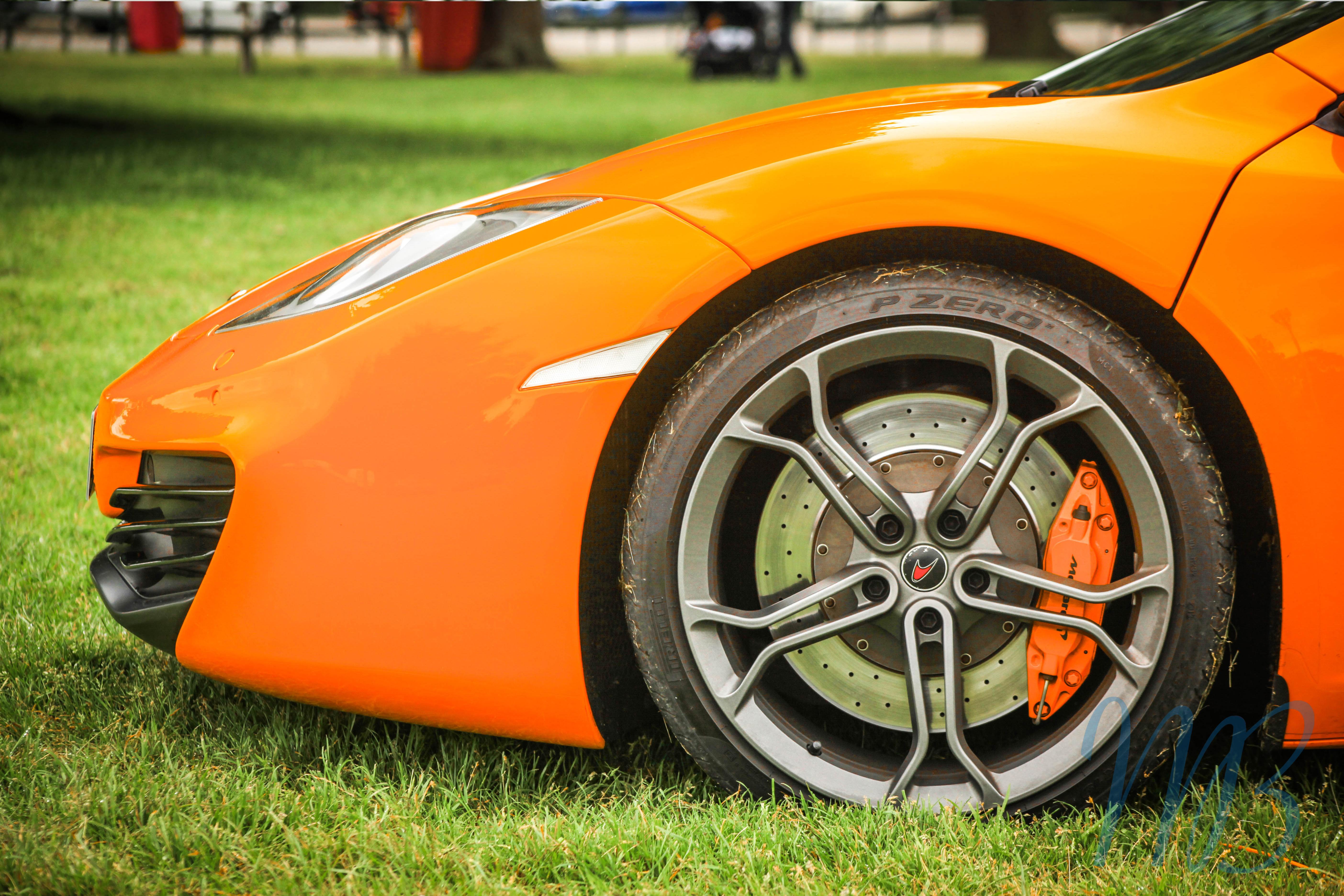 front of an orange mclaren