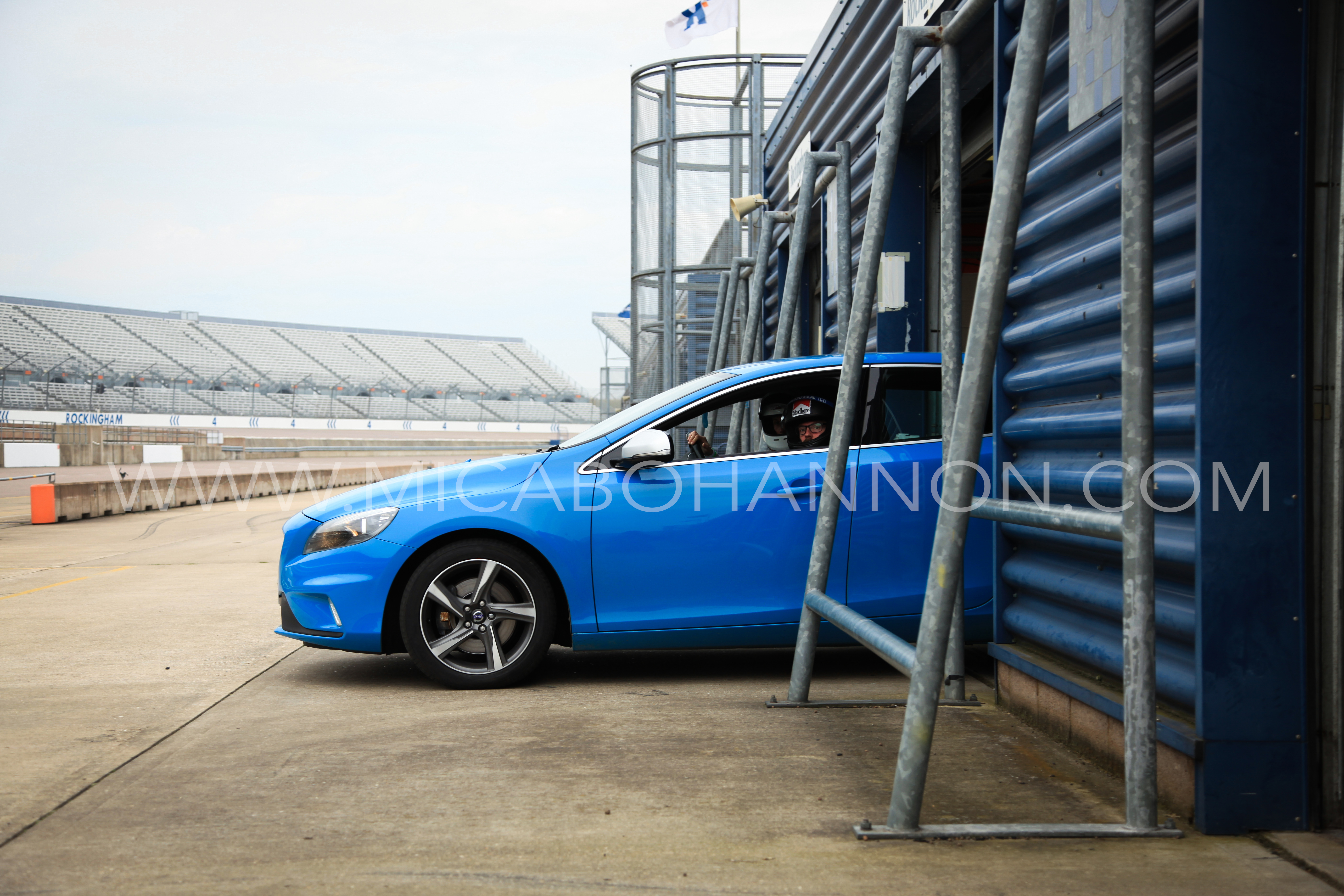 blue volvo coming out of pit garage