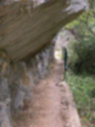 Photo montrant le chemin en corniche dans les gorges de San Jaume et les rochers qui le dominent.