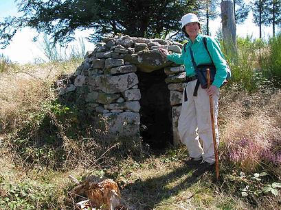 Randonneuse à côté d'un petit abri en pierres sèches.