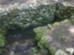 Point d'eau bâti de pierres sèches et équipé d'un escalier, le long du chemin.