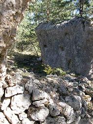 Vestiges du village protohistorique, vue montrant l'utilisation des parois naturelles pour fixer des poutres