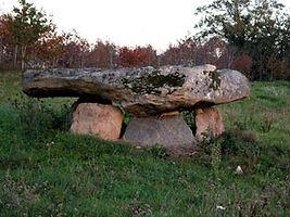 Vue de l'arrière du dolmen de la Lue, dalle massive, lumière crépusculaire.