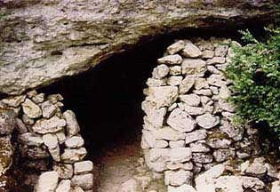 Vestiges du village protohistorique, vue d'un abri trogloditique sommaire, grotte avec petits murs bâtis.