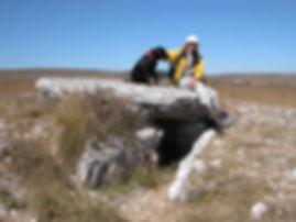 Randonneur et son chien assis sur un dolmen dans un lieu désertique.