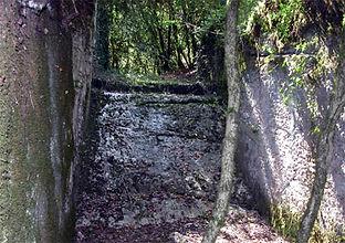 En dessous de l'arche de pierre, un bief de moulin, vu de dessous.