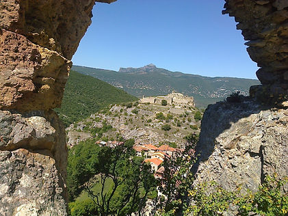 Vue lointaine du massif du Bugarach par la fenêtre en ruines d'un château chathare. Un deuxième château se trouve au deuxième plan.