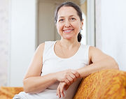 Smiling ordinary mature woman in home in