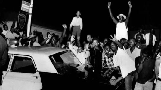 Demonstrators push against a police car after rioting erupted in a crowd of 1,500 in the Los Angeles area of Watts, triggered by the arrest of a black person on charges of drunken driving. (Credit: AP Photo)