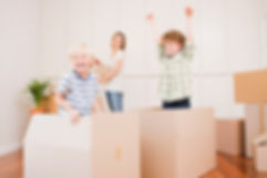 Kids jump out of moving boxes while mom packs up the old kichen in anticiaption for her new kitchen cabinets from click cabints