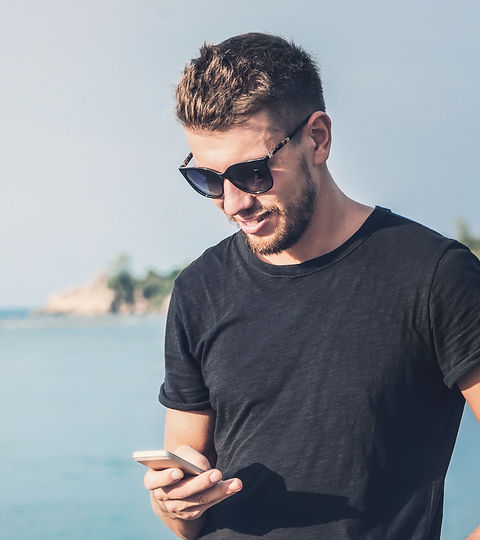 Handsome man in sunglasses holding mobil
