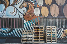 Pallets standing up against a mural wall