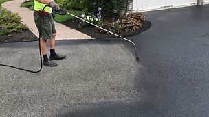 Sparying oil sealer on driveway