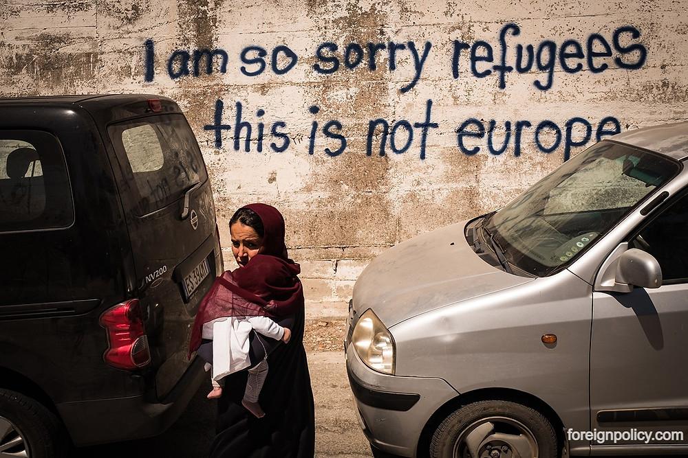 İki panevan araç arasında  kucağında bir bebekle bir kadın, duvarda i am so sorry refugees this is not europe yazıyor