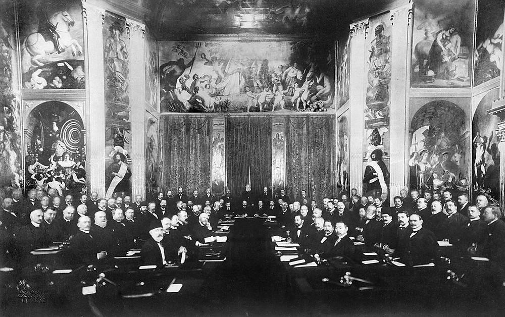 konferastan siyah beyaz bir fotoğraf, üyler karşılıklı oturuyor, salon duvar resimleriyle dolur