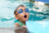 Young boy with paddle board enjoys swimming lessons