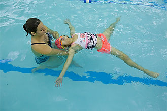 Young girl with swimming instructor learning to float in pool