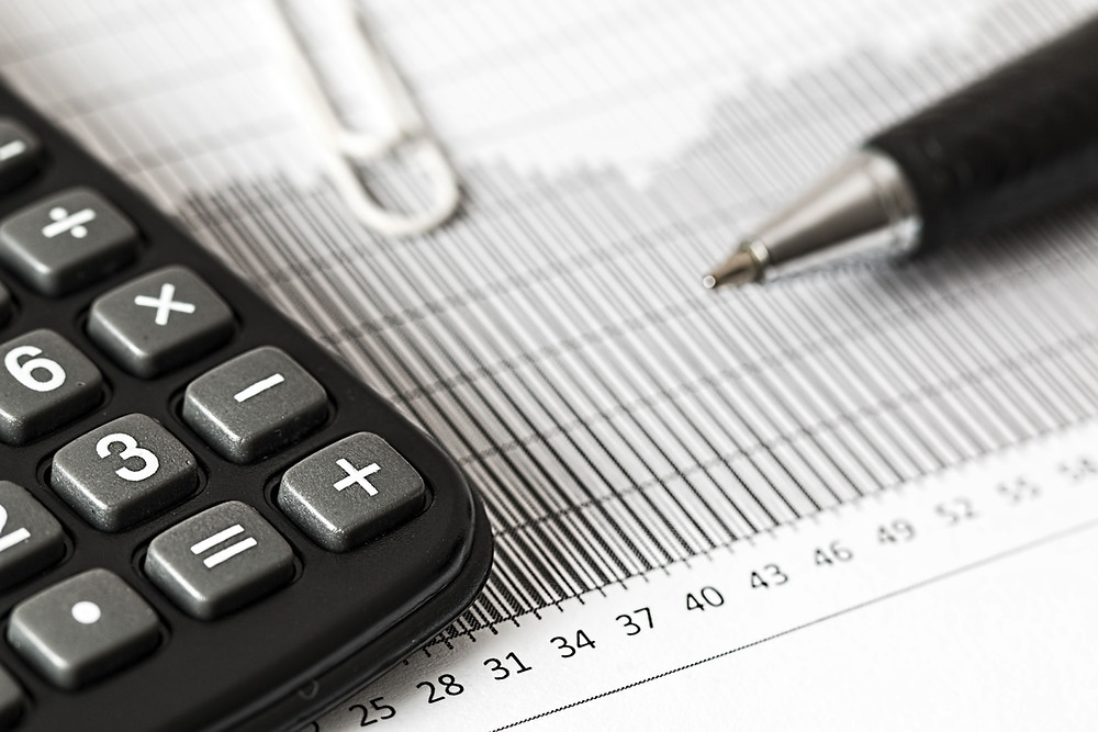 Calculator, pen, and tax forms