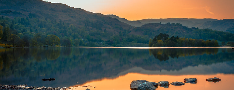 Still waters in Lake District with orange sky