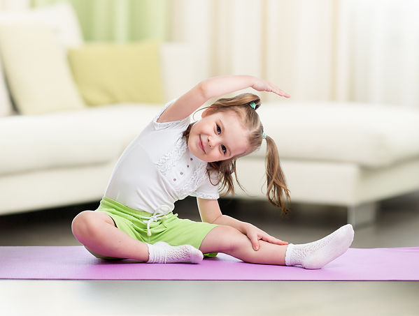 Child doing fitness exercises at home in