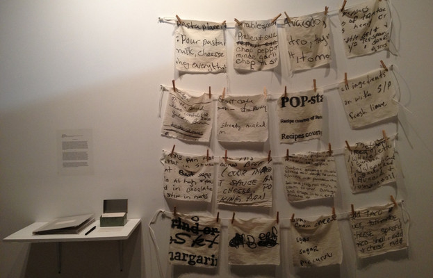 Following the cooking workshops, Rooneypainted a series of napkins as a celebration of these women's stories, their recipes, and their collaboration. Each napkin includes an excerpt of one woman's recipe,traced and hand-painted onto the fabric. The napkins were installed atHot Wood Arts Centerin 2015 as part of theEngaging Artistsculminating exhibition. Beside the napkins is thecookbook produced thatincludes the original recipe submissions and other materials from their work together.